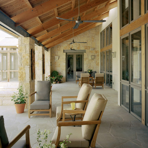 Tuscan Stone Porch Photo In Austin With A Roof Extension