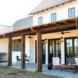 Idee per un portico country di medie dimensioni e dietro casa con lastre di cemento e un parasole