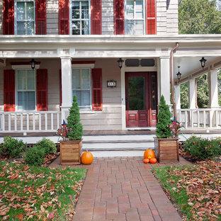 Idee per un grande patio o portico vittoriano davanti casa con pavimentazioni in mattoni e un tetto a sbalzo