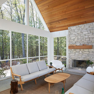 Inspiration for a large 1960s concrete screened-in side porch remodel in Grand Rapids with a roof extension