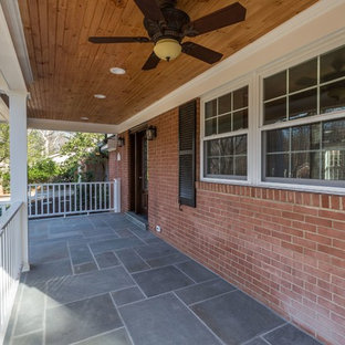 This is an example of a mid-sized traditional concrete paver front porch design in DC Metro with a roof extension.