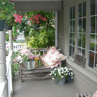 Photo of a mid-sized shabby-chic style front yard verandah in Toronto with decking and a roof extension.