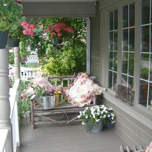 Shabby chic-inspirerad inredning av en mellanstor veranda framför huset, med trädäck och takförlängning