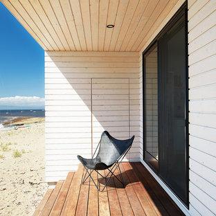 Ispirazione per un piccolo patio o portico nordico dietro casa con pedane e un tetto a sbalzo