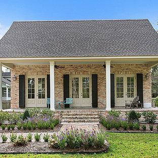Immagine di un grande portico american style nel cortile laterale con pavimentazioni in mattoni e un tetto a sbalzo
