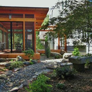 Cette image montre un petit porche arrière asiatique avec une moustiquaire et une terrasse en bois.