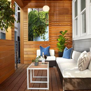Ejemplo de terraza clásica renovada, de tamaño medio, en anexo de casas y patio delantero, con entablado