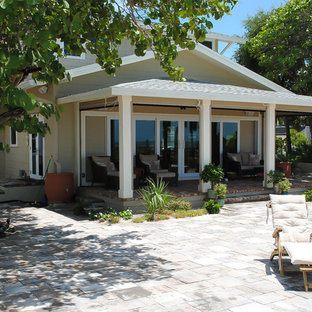 This is an example of a mid-sized traditional back porch design in Tampa with a roof extension.