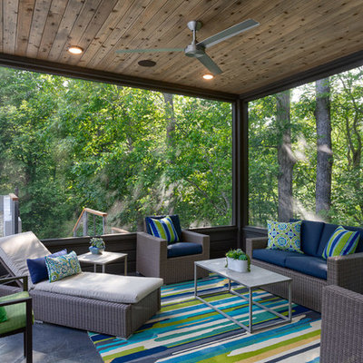 This is an example of a coastal screened-in porch design in Other with a roof extension.