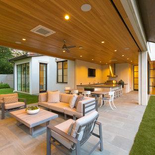Idee per un ampio portico mediterraneo dietro casa con pavimentazioni in pietra naturale e un tetto a sbalzo