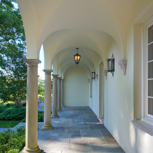 This is an example of a mediterranean stone front porch design in DC Metro with a roof extension.