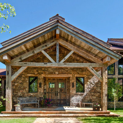 This is an example of a rustic stone front porch design in Salt Lake City with a roof extension.
