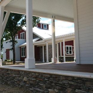 Foto di un ampio patio o portico country davanti casa con pedane e un tetto a sbalzo