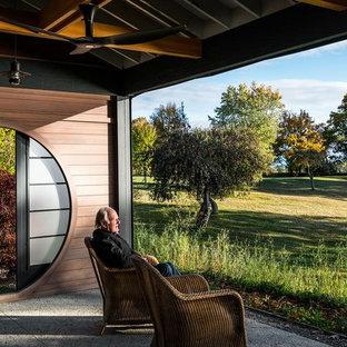 Foto di un portico etnico di medie dimensioni e dietro casa con un portico chiuso, lastre di cemento e un tetto a sbalzo