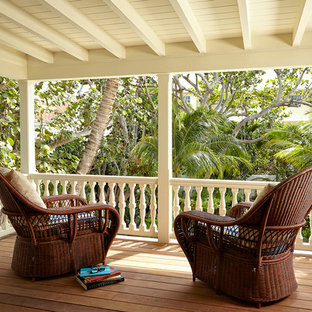 This is an example of a mediterranean porch design in Miami with decking and a roof extension.