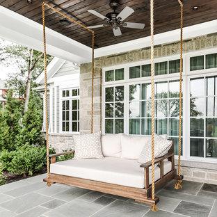 Bild på en vintage veranda framför huset, med naturstensplattor och takförlängning