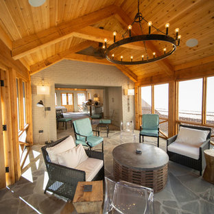 Large arts and crafts stone back porch idea in Other with a fireplace and a roof extension
