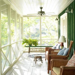 Esempio di un patio o portico country di medie dimensioni e davanti casa con un portico chiuso, pedane e un tetto a sbalzo