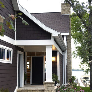 Mid-sized classic stone front porch idea in Other with a roof extension