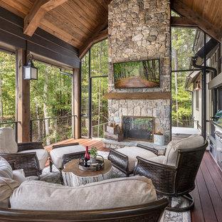 Diseño de terraza rural, extra grande, en anexo de casas, con chimenea y entablado