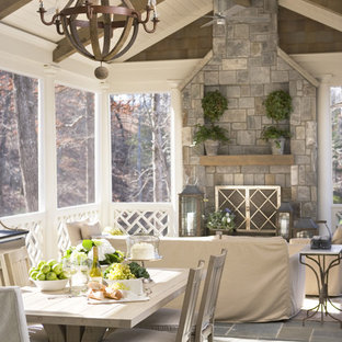 Mid-sized coastal stone screened-in back porch idea in Other with a roof extension