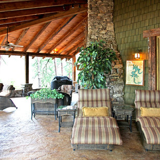 Inspiration for a large rustic stamped concrete back porch remodel in Atlanta with a fire pit and a roof extension
