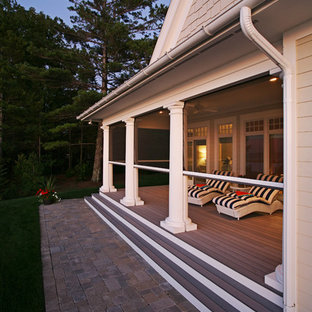 Huge elegant screened-in back porch photo in Grand Rapids with decking