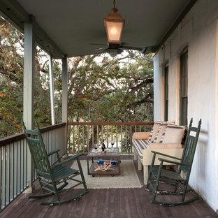 Immagine di un portico country davanti casa e di medie dimensioni con pedane e un tetto a sbalzo