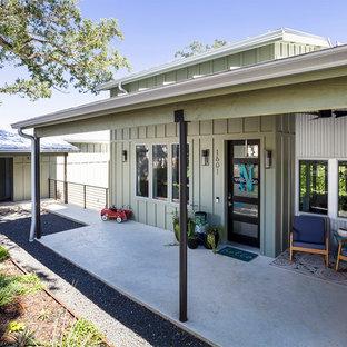 Modelo de terraza campestre, de tamaño medio, en anexo de casas y patio delantero, con jardín de macetas y losas de hormigón