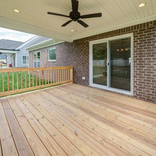 Idee per un portico american style dietro casa con pedane, un tetto a sbalzo e parapetto in legno