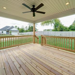 Immagine di un portico american style dietro casa con pedane, un tetto a sbalzo e parapetto in legno