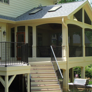 This is an example of a large transitional screened-in back porch design in Raleigh with a roof extension.