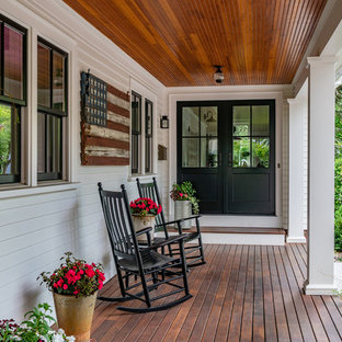 Esempio di un grande portico country davanti casa con un giardino in vaso, pedane e un tetto a sbalzo