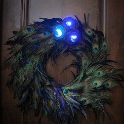 The Firefly Garden - Mad Haberdashery Wreath - Large - Add a splash of blue to your home with a beautiful 16 or 22 inch wreath of peacock feathers. This playful departure from traditional evergreen decor, featuring blue and iridescent peacock feathers is illuminated with tiny blue LED lights which uses3 replaceable AA batteries . The arrangement has blueberry and crystal accents to bring country charm to any setting.