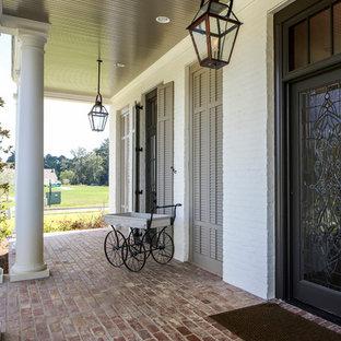 Idee per un ampio portico classico davanti casa con pavimentazioni in mattoni e un tetto a sbalzo