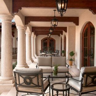 На фото: большая веранда на заднем дворе в средиземноморском стиле с покрытием из каменной брусчатки и навесом с