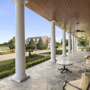 Huge elegant stone back porch photo in Orlando with a roof extension