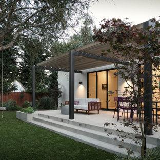 Foto di un portico contemporaneo dietro casa con lastre di cemento e una pergola