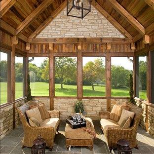 Immagine di un portico stile rurale con un tetto a sbalzo e un portico chiuso