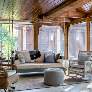 This is an example of a cottage tile screened-in porch design in Atlanta with a roof extension.