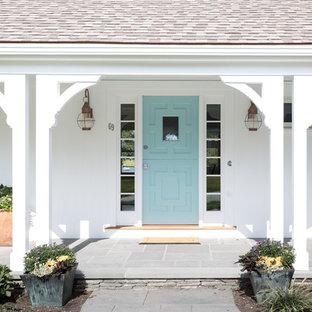 Idee per un patio o portico costiero di medie dimensioni e davanti casa con un giardino in vaso, pavimentazioni in pietra naturale e un tetto a sbalzo