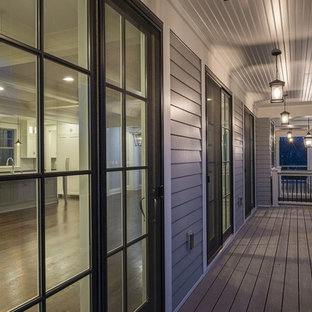 This is an example of a large beach style front porch design in Minneapolis with decking and a roof extension.
