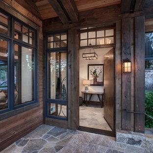 Idee per un grande portico davanti casa con pavimentazioni in pietra naturale e un tetto a sbalzo