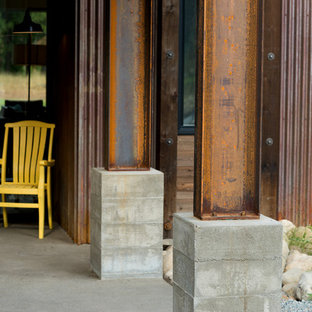 Inspiration for a mid-sized industrial concrete front porch remodel in Seattle with a roof extension