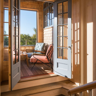 This is an example of a small beach style screened-in back porch design in Boston with decking and a roof extension.