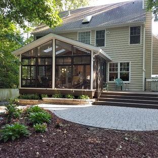 Réalisation d'un porche arrière craftsman de taille moyenne avec une moustiquaire, des pavés en brique et une extension de toiture.