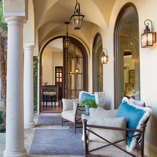 Mid-sized tuscan stone back porch idea in Dallas with a roof extension
