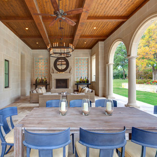 Inspiration for a huge mediterranean tile back porch remodel in Dallas with a fire pit and a roof extension