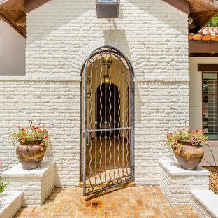Esempio di un grande portico mediterraneo davanti casa con fontane, pavimentazioni in mattoni e un parasole