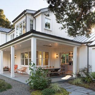 Esempio di un portico country di medie dimensioni e nel cortile laterale con pavimentazioni in pietra naturale e un tetto a sbalzo